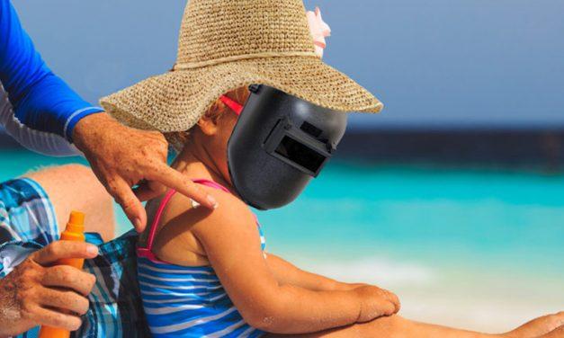 Înainte de plajă. Copil dat cu 4 straturi de protecție solară, echipat cu mască de sudură și pălărie