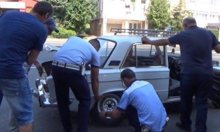 VIDEO. Șofer bătrân rămas în pană, ajutat de doi polițiști să schimbe roata mașinii
